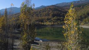 Top view of small lake with reflection of mountains in autumn. Shot. Beautiful view with reflection of colorful. Mountains in lake in autumn sunny day. Beauty stock video