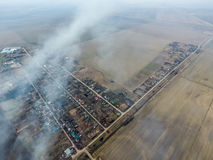 Top view of the small village. Smoke from the burning of straw i stock photo