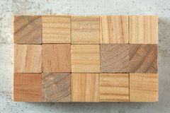Top view - 15 small wooden cubes arranged to 3 x 5 grid, on concrete board. Letters can be added.  royalty free stock photo