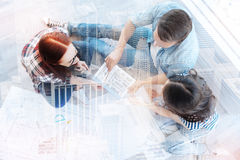 Top view of smart coworkers in the office. Brilliant idea. Top view of young enthusiastic coworkers sitting together covered with papers and talking about future Royalty Free Stock Photography