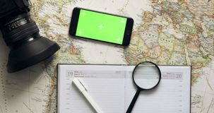 Top view traveler planning holiday using mobile phone app vintage desk from above. Top view. smart phone with green screen lies on the diary. Planning holidays stock footage