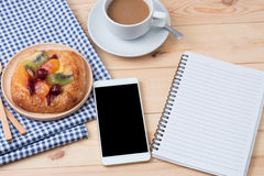 Top view of Smart phone with notebook and cup of latte art coffe. E on wooden background royalty free stock photo