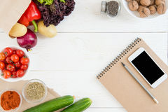 Top view of smartphone with blank screen, empty notebook with pencil and fresh ingredients Royalty Free Stock Image