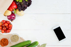 Top view of smartphone with blank screen and fresh raw vegetables. On wooden table Stock Photos