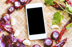 Top view smartphone with collection of fresh onions and chilis Stock Images
