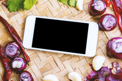 Top view smartphone with collection of fresh onions and chilis Stock Photography