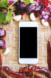 Top view smartphone with collection of fresh onions and chilis Royalty Free Stock Image