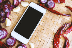 Top view smartphone with collection of fresh onions and chilis Stock Image