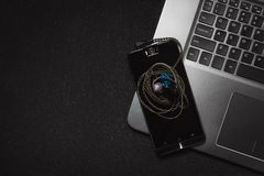 Top view smartphone with headphones and laptop keyboard on black background stock photography