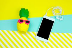 Smartphone with headphones and squishy anti stress toy pineapple in sun glasses on a stripped yellow and blue. Top view smartphone with headphones and squishy stock photos