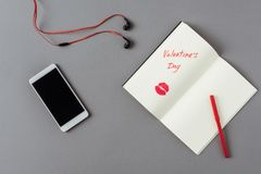 Top view of smartphone and notebook with words valentines day. On gray surface stock photo
