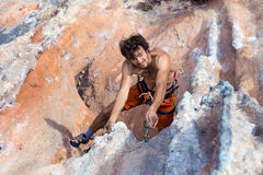 Top View of Smiling Climber hanging high on rocky Wall Royalty Free Stock Image