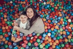Top view. Smiling mom and son in pool with balls. Hugging each other. Family rest, leisure. Spending holiday together with family. Entertainment center, mall royalty free stock photo