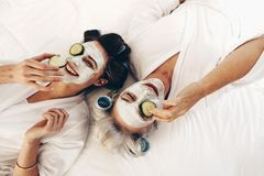 Top view of smiling mother and daughter lying on bed with face p. Two women in bathrobes lying on bed wearing beauty face pack with cucumber slices. Mother and stock image