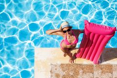 Woman with pink inflatable mattress at poolside. Top view of smiling woman in sunglasses standing at poolside, holding pink inflatable mattress and looking at Stock Photo