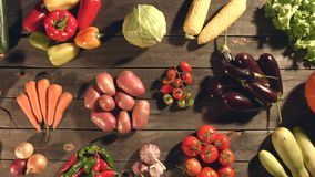 Many different vegetables lie on the table. Top view. The smooth glide of the camera  from left to right  along the old village table with a variety of stock footage