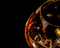 Top of view of snifter of brandy in elegant typical cognac glass on black background with red reflection Stock Images
