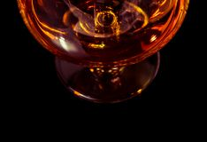 Top of view of snifter of brandy in elegant typical cognac glass on black background Royalty Free Stock Image