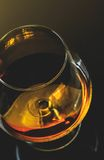 Top of view of snifter of brandy in elegant typical cognac glass on dark background with golden reflection Stock Photo