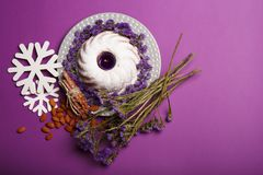 Top view of a plate with a ring cake, a candle, almond, cinnamon, snowflakes, twigs of flowers on a violet background. Top view of snowflakes, almond, sticks of Stock Photography