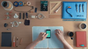 Top view software engineer is using cell phone smartphone on his desk full of equipment green screen stock footage