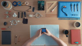 Top view software engineer is using cell phone smartphone on his desk full of equipment stock footage