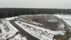 Top view of the solid waste landfill. Flying over the dump. Top view of the solid waste landfill, located in a coniferous forest. Flying over the dump. Concept stock footage