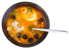 Top view of Solyanka fish soup in bowl with spoon. Top view of Solyanka russian traditional spicy and sour soup with fish in bowl with spoon isolated on white Royalty Free Stock Image
