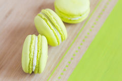 Top view of some green macaroons on wooden background. Top view of some green macaroons with cream ganache arranged diagonally on wooden background. Shallow Royalty Free Stock Photos