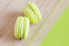 Top view of some green macaroons on wooden background. Top view of some green macaroons with cream ganache arranged diagonally on wooden background. Shallow royalty free stock photography