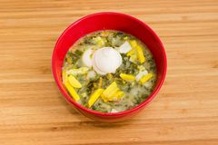 Top view of sorrel soup with egg and sour cream. Top view of sorrel soup also known as green borscht with chopped egg and sour cream in red bowl on a wooden Stock Image