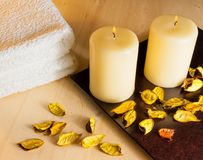 Top of view of spa massage border background with towel stacked, perfumed leaves, candles and sea salt Stock Photo