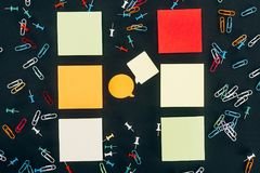 Top view of speech bubbles, colorful paper clips and blank notes. On black stock photos