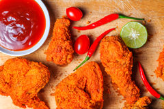 Top view of spicy fried chicken with tomatoes, chili, lime and ketchup on wooden tray. Background royalty free stock image