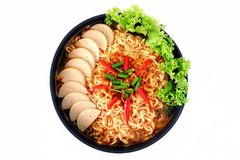 Top view of Spicy Instant noodles soup. Top view of Spicy Instant noodle soup with fermented pork sausage and vegetables in a black bowl on white background Stock Photo