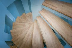 Top view of spiral wooden staircase surrounded with blue wall. royalty free stock image