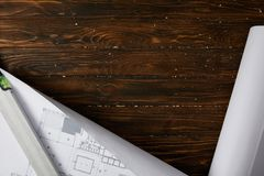 Top view of spirit level and blueprint on wooden brown table stock photography