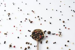 Peppercorns. Top view of spoon with spilled peppercorns isolated on white Royalty Free Stock Photos