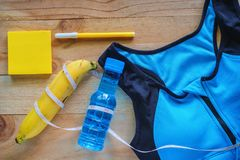 Top view of sport bra, fresh drinking water, banana, note pad, pen and measure tape on wooden table. For exercise and fitness concept Stock Photos