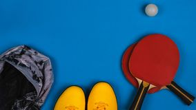 Top view on the sport composition with sneakers, jacket, tennis rocket with ball on the bright blue background, horizontal stock photos
