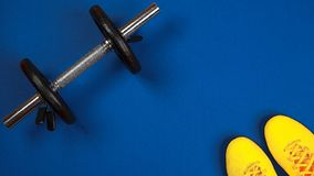Top view on the sport set for gym with fashion yellow snickers and silver dumbbell on the blue background. Flat lay, top view, royalty free stock photography