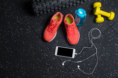 A top view of sportive accessories for gym training. Sport shoes, dumb-bells, bottle, and phone on a black background. Stock Image