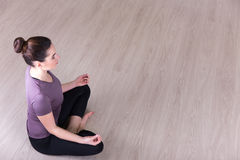 Top view of sporty woman sitting in yoga pose on the floor Royalty Free Stock Images