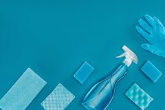 Top view of spray bottle with blue washing sponges. Isolated on blue stock images