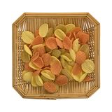 Wicker basket of vegetable chips on a white background. Top view of a square wicker basket filled with vegetable chips isolated on a white background Stock Photo