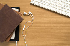 top view of stack of notebook with earphone and computer keyboar Stock Photography