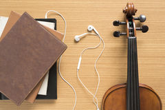 top view of stack of notebook with earphone and violin Royalty Free Stock Images