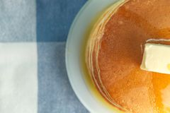 Top view of stack of pancake with honey and butter on top. Close up photo of stack of pancakes with honey and piece of butter on plate which stands on napkin Royalty Free Stock Photo