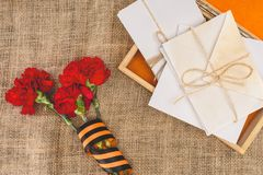 Top view of stacks of letters on photo frame and carnations wrapped by st. george ribbon royalty free stock photography