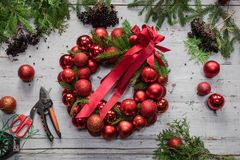 Top view of stages of making Christmas wreath with fir branches and decorative red balls on wooden rustic tabletop. Toned stock photo